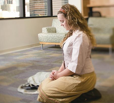 young-woman-kneeling-floor-praying_1296810_inl